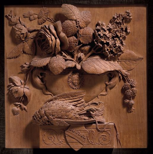 The Wettin Still-Life: Carved panel relief still life with a bird and a vase containing roses, lilacs, daisies and ranunculi, resting on a ledge bearing the arms of the House of Wettin